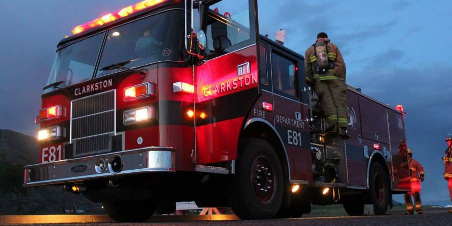 Firefighters stand around Clarkston Fire Department engine E81 in the evening with the emergency lights on