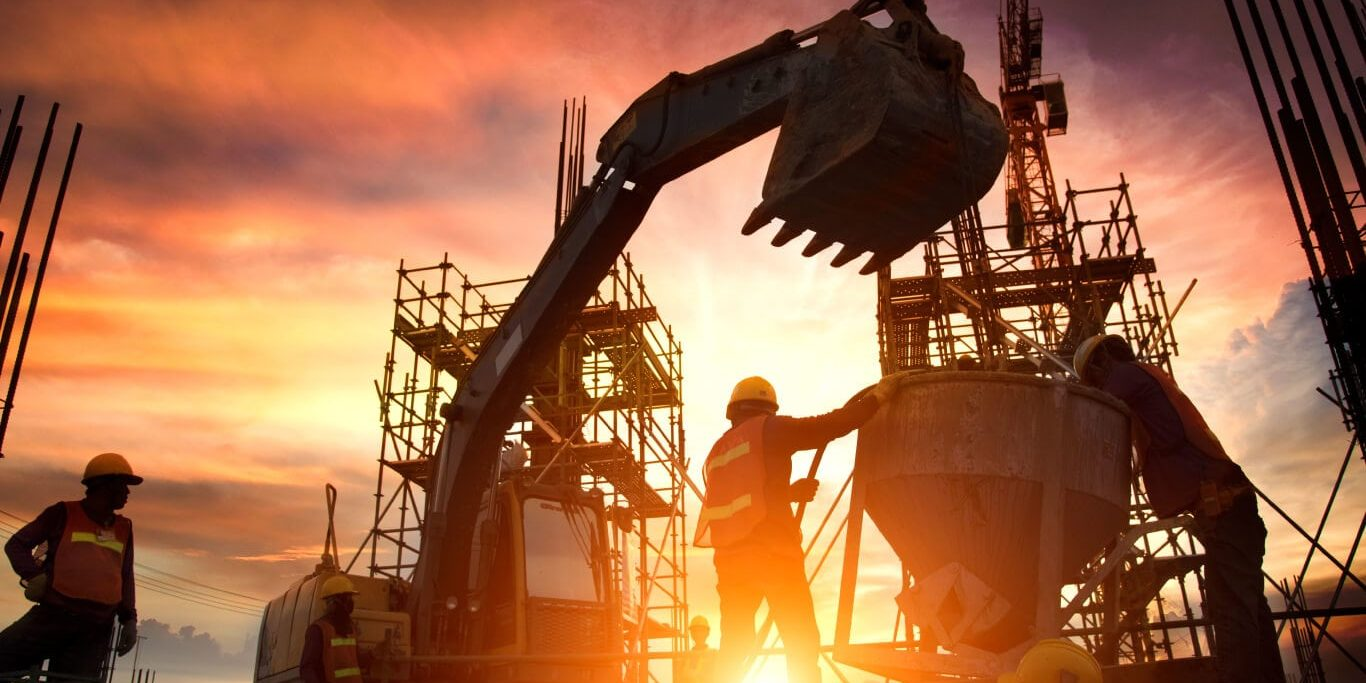 Group of construction workers manage a worksite at sunset, with an excavator and a cement mixer