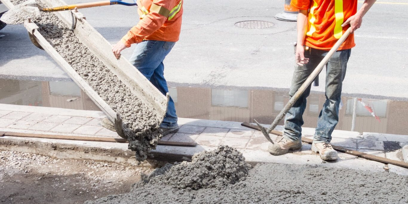 Two public works employees pouring concrete for a sidewalk