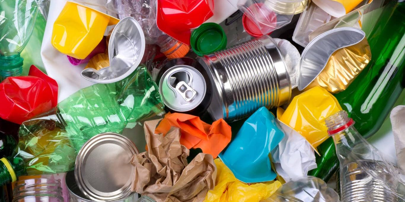 Top view of a bin of recycling waste, including cans, bottles, plastic, and paper waste